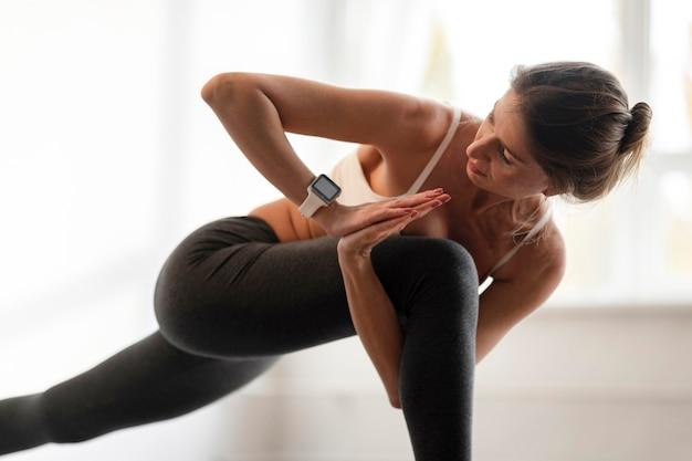 Donna che esercita posizioni yoga a casa