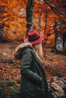 Donna che esplora la foresta autunnale