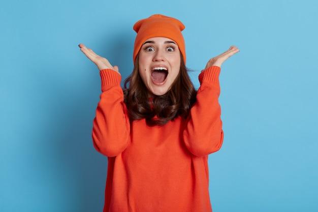 La donna che esprime piacevole sorpresa, alza le mani e guarda la telecamera con uno sguardo scioccato positivo, tiene la bocca aperta, indossa un cappello arancione e un maglione, isolato sopra il muro blu