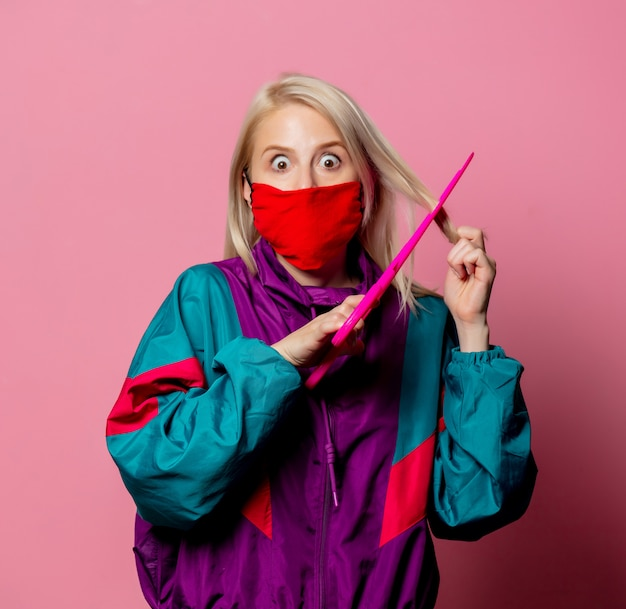 Donna in maschera e vestiti anni '80 con grandi forbici in rosa