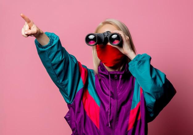 Donna in maschera e abiti anni '80 con il binocolo in rosa