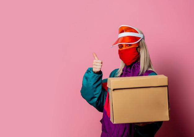 Donna in maschera e abiti anni '80 con scatola di consegna in rosa