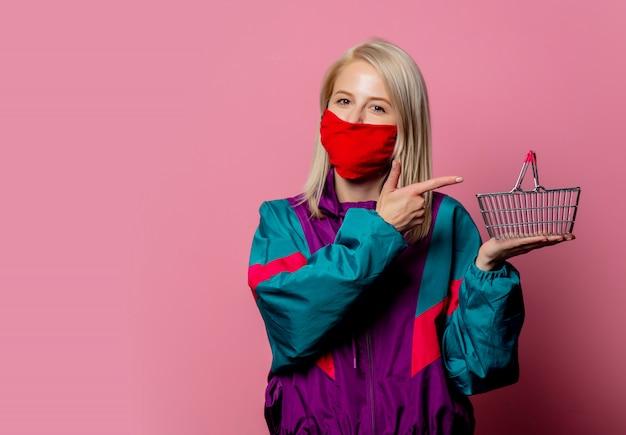 Donna in maschera e vestiti degli anni '80 con il carrello in rosa