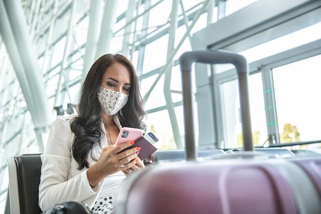 La donna con la maschera facciale controlla il suo telefono mentre aspetta un aereo in una sala, con in mano un passaporto e una carta d'imbarco.