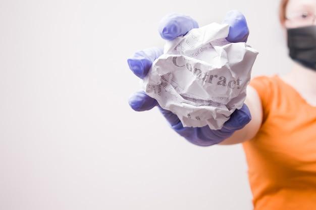 La donna in una maschera e guanti tiene un contratto di disoccupazione sgualcito