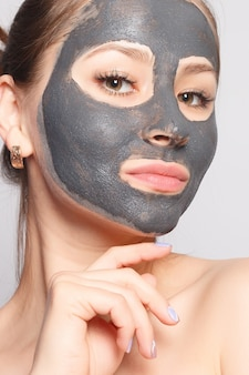 Maschera per il viso della donna. ritratto di bella ragazza che rimuove la maschera peeling nera cosmetica dalla pelle del viso. primo piano di giovane donna attraente con trucco naturale e maschera di buccia cosmetica sul viso. alta risoluzione