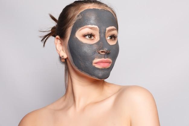Maschera per il viso della donna. ritratto di una bella ragazza che rimuove la maschera peeling nera cosmetica dalla pelle del viso. primo piano di giovane donna attraente con trucco naturale e maschera di buccia cosmetica sul viso. alta risoluzione