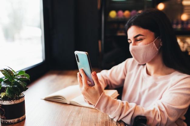 Donna in maschera facciale sorridente, leggere il telefono, scrivere sul taccuino