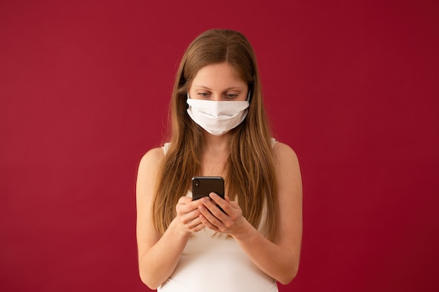 Donna in maschera per il viso scrivere messaggi sul cellulare con sfondo rosso