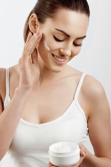 Donna viso cura della pelle ritratto di attraente giovane femmina applicare crema