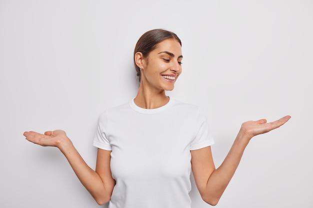 La donna affronta una scelta difficile allarga i palmi finge di tenere qualcosa vestito con una maglietta casual su bianco