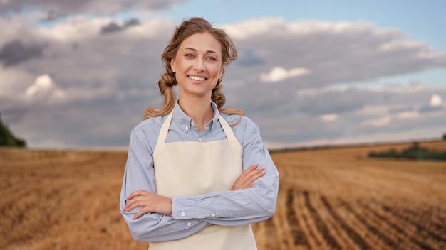 Grembiule agricoltore donna in piedi terreni agricoli sorridente agronomo femmina specialista agricoltura agroalimentare felice lavoratore indoeuropeo positivo campo agricolo