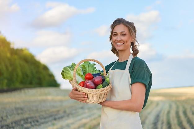 Donna agricoltore grembiule permanente di terreni agricoli sorridente agronomo femmina specialista agricoltura agroalimentare felice positivo lavoratore caucasico campo agricolo
