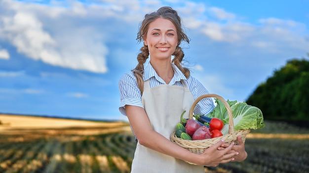 Grembiule da agricoltore donna in piedi terreno coltivabile sorridente agronomo femminile specialista in agricoltura agroalimentare