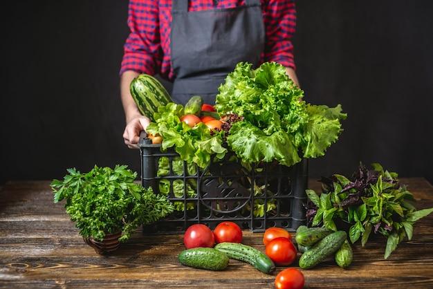 L'agricoltore della donna sta tenendo una scatola con verdure fresche e insalata verde