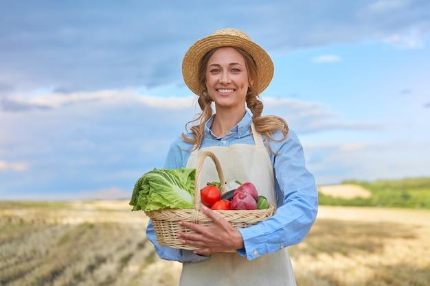 Donna agricoltore cappello di paglia grembiule in piedi terreni agricoli sorridente femmina agronomo specialista agricoltura agroalimentare campo agricolo lavoratore indoeuropea positivo felice