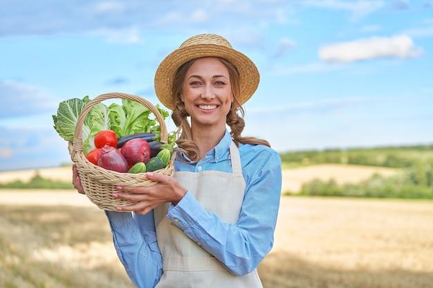 Contadina cappello di paglia grembiule permanente di terreni agricoli sorridente agronomo femmina specialista agricoltura agroalimentare felice positivo lavoratore caucasico campo agricolo