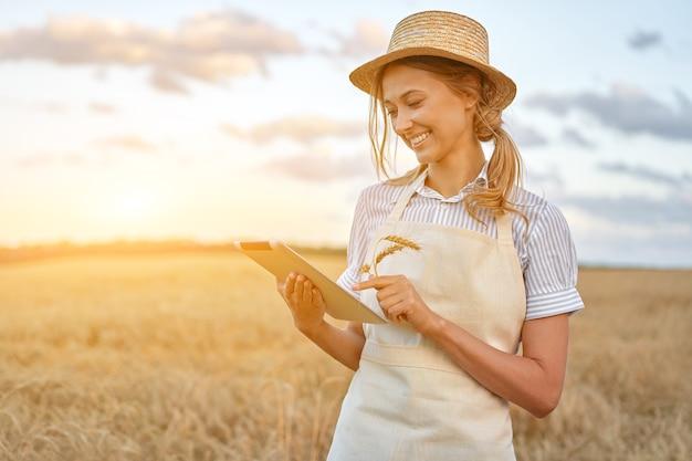 Donna agricoltore cappello di paglia agricoltura intelligente in piedi terreni agricoli sorridente utilizzando la tavoletta digitale agronomo femminile specialista ricerca monitoraggio analisi dati agribusiness