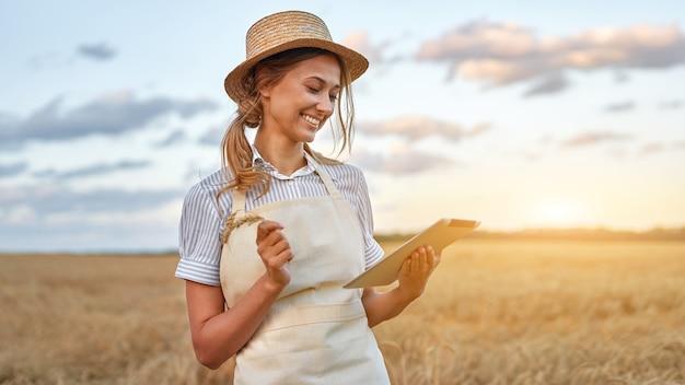 Donna agricoltrice cappello di paglia agricoltura intelligente in piedi terreni agricoli sorridenti utilizzando tablet digitale agronomo specialista ricerca analisi monitoraggio dati agribusiness