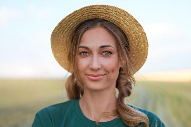 Donna contadino cappello di paglia in piedi terreni agricoli sorridente femmina agronomo specialista agricoltura agroalimentare felice lavoratore indoeuropeo positivo campo agricolo
