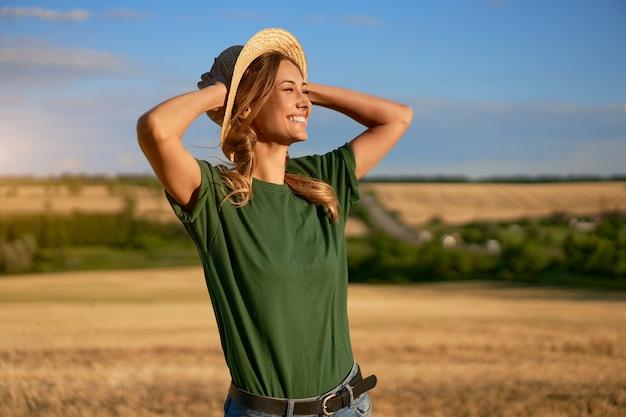 Donna contadina cappello di paglia in piedi terreno coltivabile sorridente femmina specialista agronomo agricoltura agroalimentare