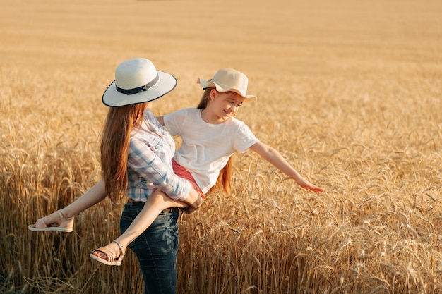 Contadina con cappello tiene in braccio il suo bambino donna e bambino nella famiglia del campo di grano dorato...