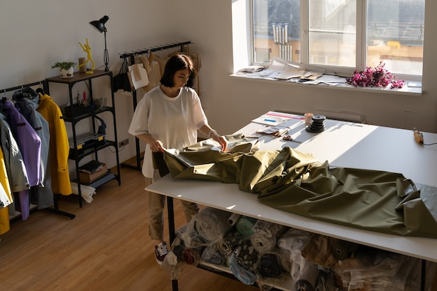 La stilista della donna lavora con il tessuto in un panno tagliato da fogna su misura femminile dell'atelier in studio dell'officina