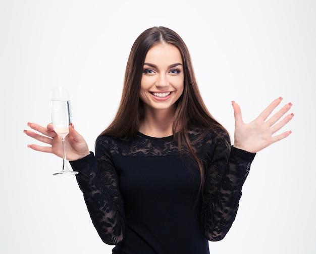 Donna in vestito da modo che tiene vetro con champagne