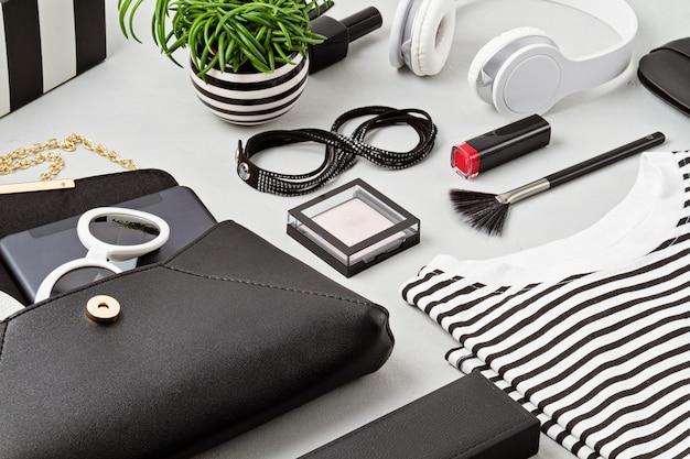Completo e accessori moda donna, borsetta, blocco note, trucco e auricolari nei colori bianco e nero. concetto di bellezza, abbigliamento urbano e tendenze della moda. vista piana laico e dall'alto