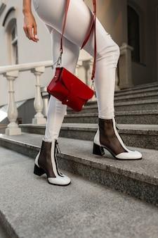 Donna in vestiti di denim bianco moda in scarpe eleganti con una borsa rossa si erge sui gradini di pietra in città.