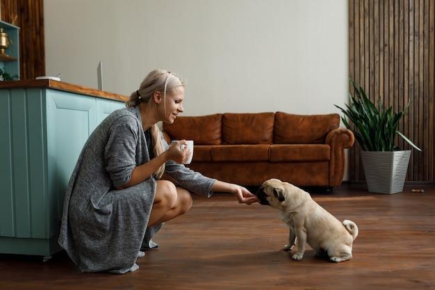 Donna che alimenta cane mentre accovacciata in cucina a casa