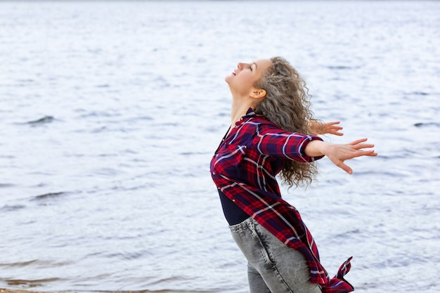 Donna che sente la brezza nell'oceano