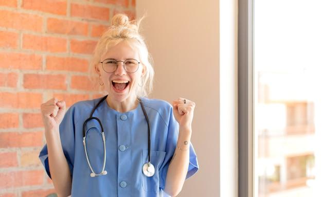 Donna che si sente scioccata, eccitata e felice, ridendo e celebrando il successo, dicendo wow!