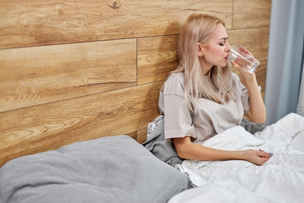 Donna che si sente male, beve acqua con farmaci in pillole, interno di casa, copia spazio. maledetta signora bionda con febbre, raffreddore o infezione da coronavirus. in camera da letto da solo