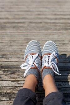 Piedi di donna in scarpe casual sullo sfondo del molo in legno