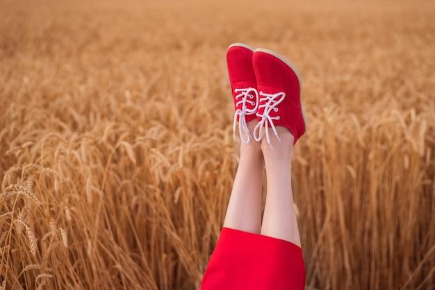 Piedi di donna in scarpe rosse divertenti sporgenti su sfondo campo di grano.