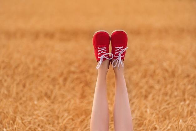 Piedi di donna su sfondo campo di grano. belle gambe sottili in scarpe rosse.