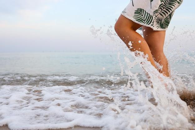 I piedi della donna camminano la vita lenta e si rilassano sulla spiaggia tropicale di sabbia con il fondo del cielo blu. vacanza e concetto di vacanza.