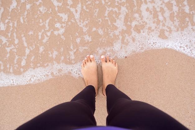Piedi della donna in piedi sulla spiaggia