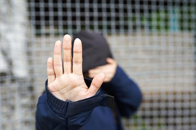 Donna dietro il recinto, primo piano della mano di una donna rifugiata