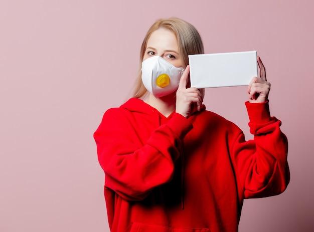 Donna in ffp2 maschera facciale standard anti-polvere tenere banner su sfondo rosa
