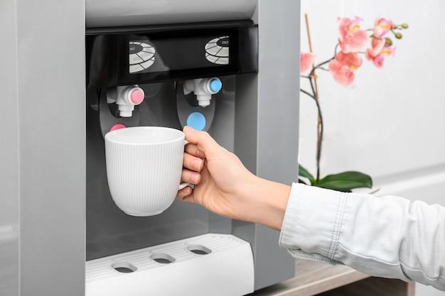 Donna che riempie la tazza dal refrigeratore d'acqua, primo piano