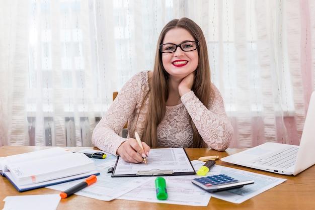 Donna che riempie il modulo fiscale individuale come parte del lavoro d'ufficio