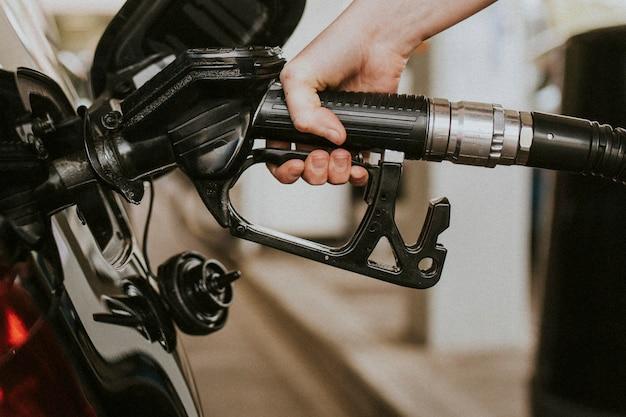 Donna che fa benzina a una stazione di servizio