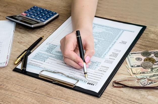 Donna che riempie il modulo fiscale con soldi e calcolatrice