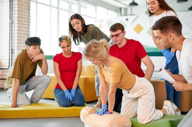 Donna nella classe di pronto soccorso che esercita la rianimazione sul manichino