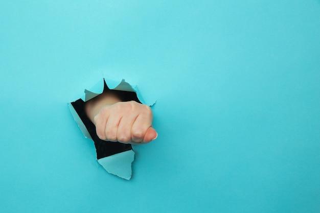 Pugno della donna che perfora attraverso il fondo di carta blu. minaccia, lotta e sport da combattimento. spingi attraverso il muro.