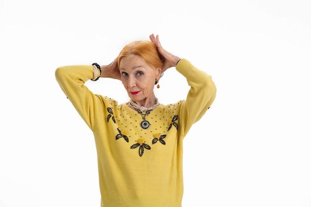 Donna che si aggiusta i capelli donna anziana su sfondo bianco consigli per sembrare più giovane