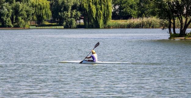 La donna galleggia in kayak sul fiume lungo la riva con alberi_