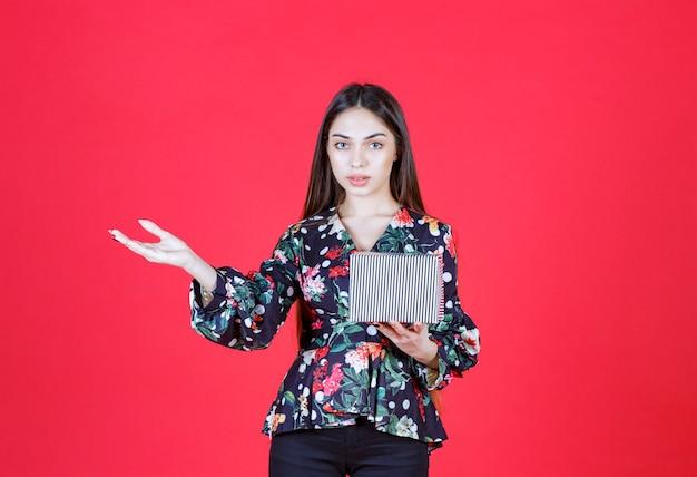 Donna in camicia floreale che tiene una scatola regalo d'argento e invita qualcuno a maneggiarla.
